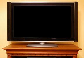 ¿Cómo puedo asegurar un televisor de pantalla plana a la mesa?